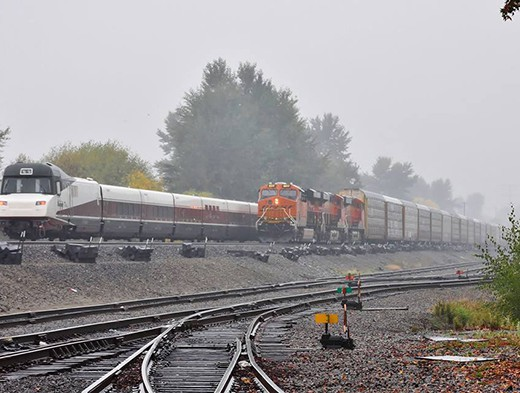 Congress averted potential end-of-the year freight and passenger rail meltdowns by approving a Positive Train Control (PTC) extension to 12/31/2018.  Here an Amtrak Cascades Service train passes a waiting BNSF freight train on a misty October morning in Renton, Washington. (Photo © Nikki Burgess 10/2015; all rights reserved)