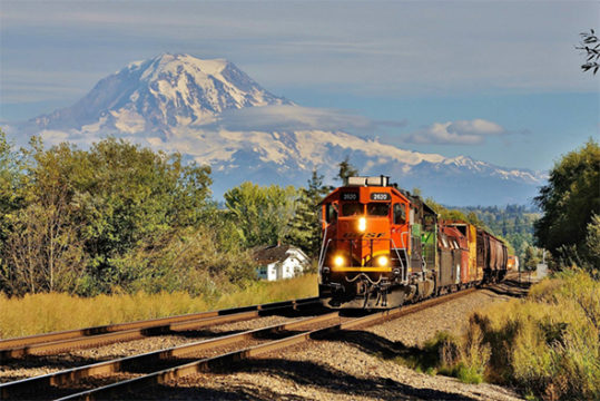 The FRA continues to focus on Positive Train Control (PTC) implementation with a new push to speed progress as well as the release of more grant funding.  A BNSF train speeds along main line track that will be part of the PTC network near Puyallup, Washington beneath Mount Rainier.  Image © 8/2016 by Nikki Burgess; all rights reserved.