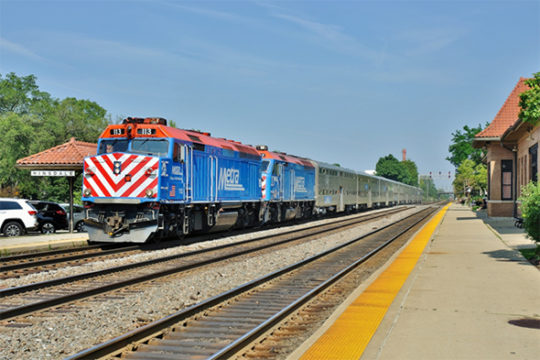 The FRA released 25 million additional dollars in federal grant money to assist local communities to enhance grade crossing safety.  Here, a Chicago Metra commuter train speeds over a busy road crossing in west suburban Hinsdale, Illinois on a sunny afternoon in August of 2014. Image © 8/2014 by Nikki Burgess; all rights reserved.