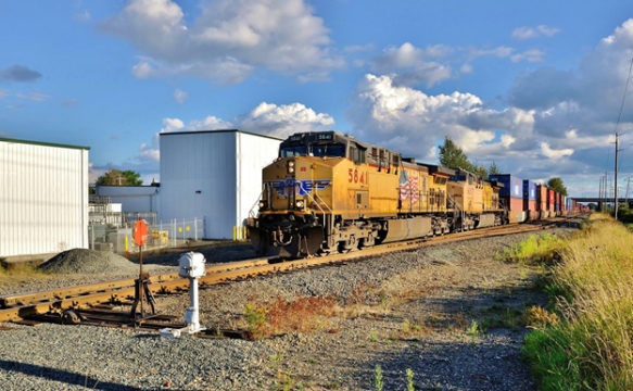 The Union Pacific Railroad, one of the two (with BNSF Railway) major western rail carriers in the United States, had its Positive Train Control implementation plan delivery to the Federal Railroad Administration announced last week. Here a UP trains heads north at Main Street in Auburn, Washington in late August. Image © 8/2016 by Nikki Burgess; all rights reserved.