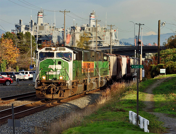 The Department of Homeland Security announced a regulatory review with public input that will address potential changes to how the agency handles dangerous goods and other safety issues, with a focus on both rail transport and port security as two of the main objectives. A BNSF freight train passes the Port of Tacoma, Washington on October 22nd, 2016. Image © 10/2016 by Nikki Burgess; all rights reserved.